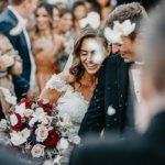 rose petals falling in front of newlywed couple