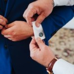 sleeve of a groom's blue suit showing Grateful Dead cufflinks a gift from his bride to be