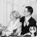 black and white photos of newlyweds sitting at their sweetheart table listening to toasts
