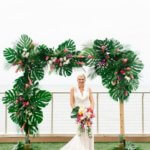 bride with tropical bouquet standing under a tropical wedding structure