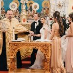 bride and groom taking their first steps as during their Greek Orthodox wedding