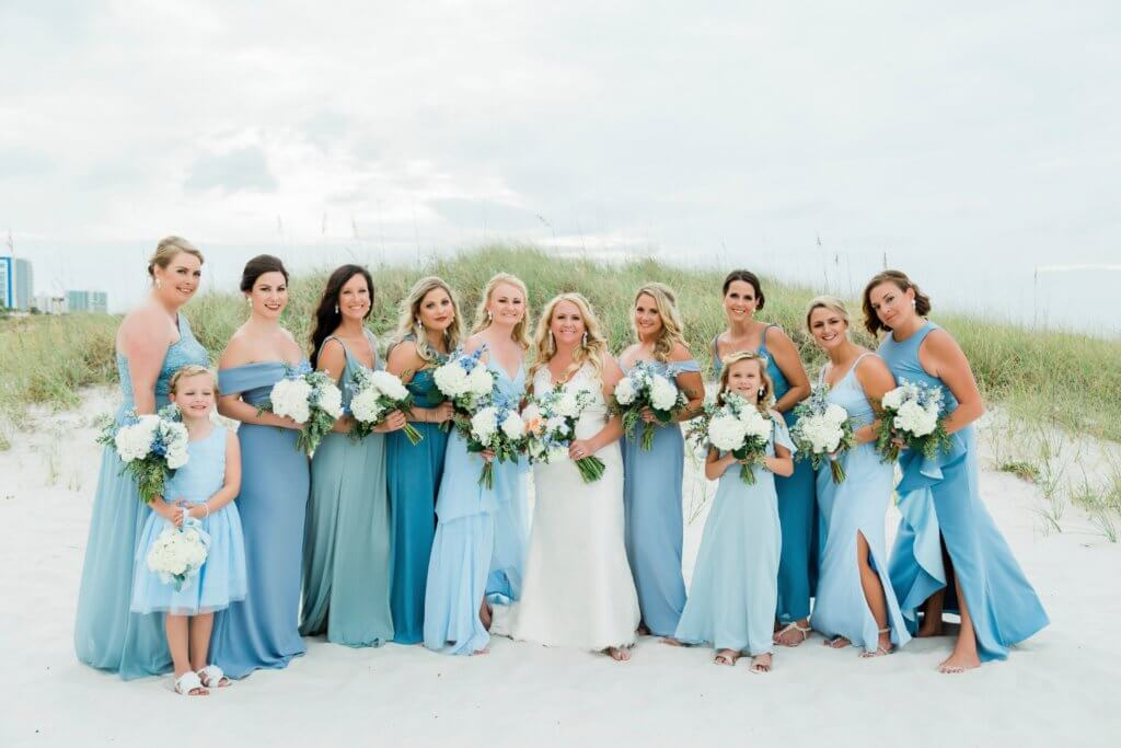 wedding party in shades of blue walking on Clearwater Beach from Special Moments Events instagram page