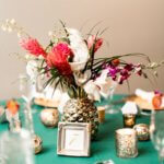 tripical floral centerpiece in a gold pineapple vase