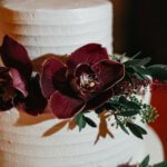 White buttercream wedding cake with burgundy orchids