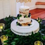 a two tiered naked wedding cake with custom cake topper
