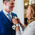 groom's mother pinning a boutonniere on her son at the Saint Petersburg Woman's Club