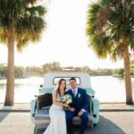 bhoh bride sitting on the back a teal vintage pickup truck with her groom