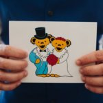 groom holding arcade from his bride with Grateful Dead Bears as bride and groom