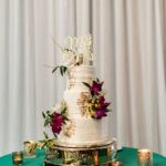 white wedding cake with gold leaf and tropical flowers