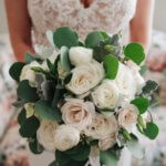 bride in a chic boho lace wedding gown holding a loose blush and ivory bridal bouquet