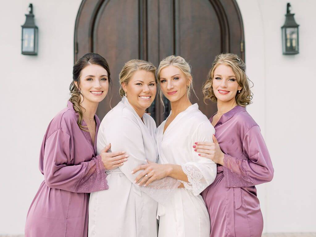 bride and bridal party wearing pink and white robes