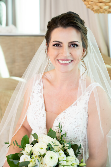 Clearwater Beach bride wearing a modern lace wedding gown carrying a white bridal bouquet
