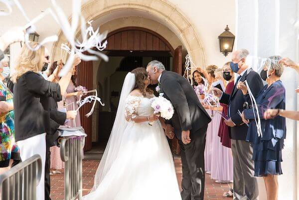 wedding guests waving white ribbon wands as the newlywed couple kisses