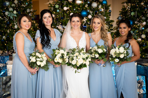 bride with her bridal party in the Opal Sands lobby during Christmas