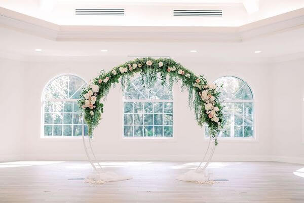white moon gate wedding arch decorated with lush greenery and pink and white flowers at Harborside Chapel