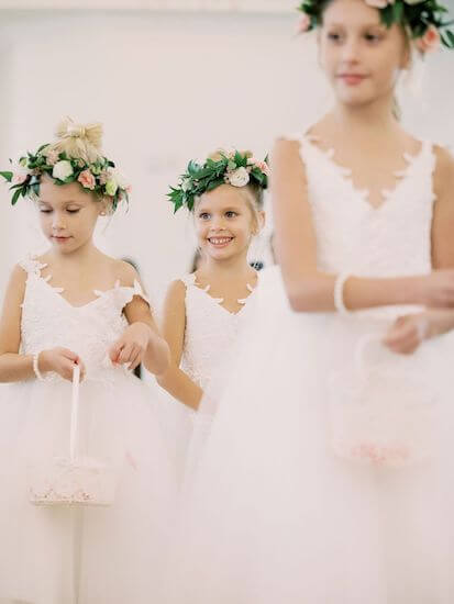 three adorable flower girls wearing lace dresses and wearing pink and white flower head pieces