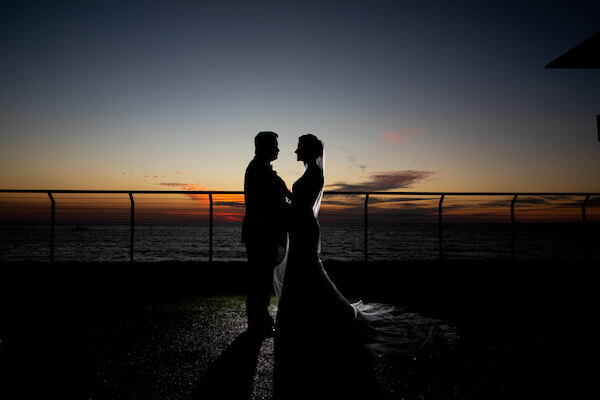 Shadowy photo of a bride and groom outside the Opal Sands Resort as the sun finishes setting and darkness falls