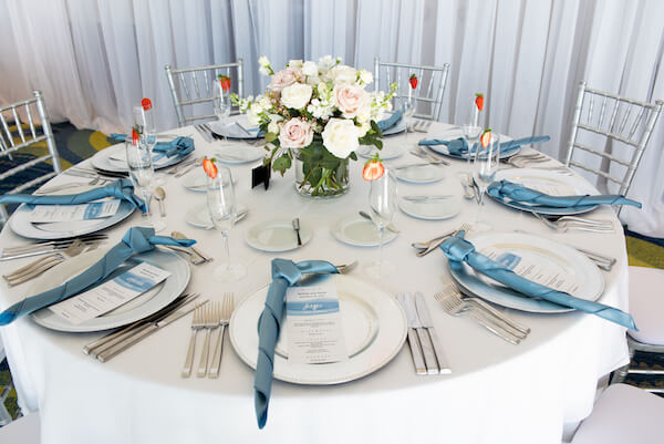 wedding reception set with silver charger plates, ice blue napkins and blue toned menu cards