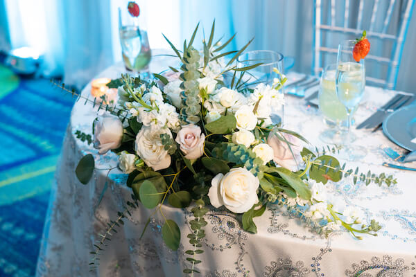 sweetheart table draped with a sequin textured linen and decorated with blush and white flowers