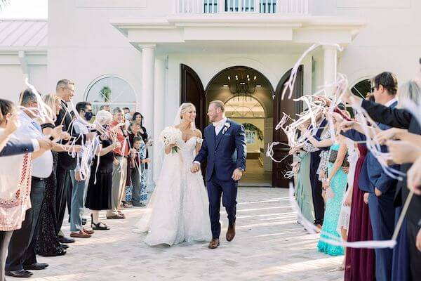 bride and groom's exit wedding with wedding guests waiving ribbon wands