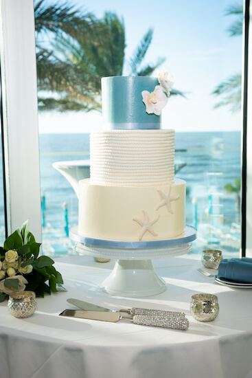 three-tiered blue and white wedding cake with starfish