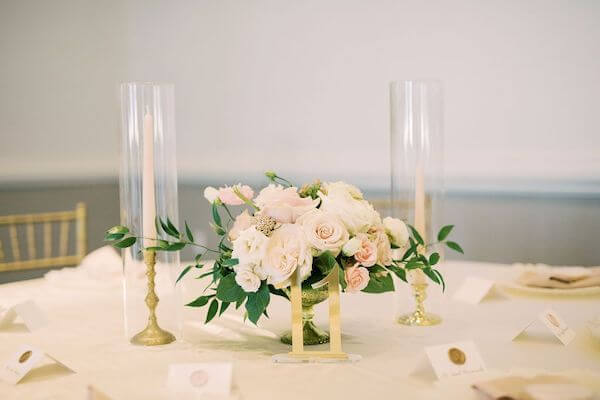 pink and white centerpiece with gold table numbers and taper candles