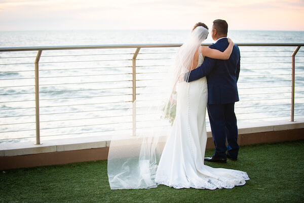 newlywed bride and groom looking over the Gulf of Mexico after their Opal Sands Resort wedding