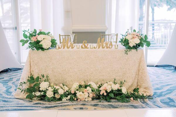 sweetheart table with lace linen and lush floral centerpieces