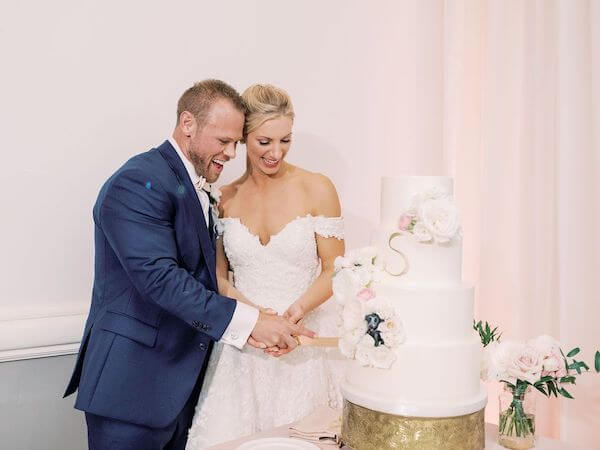 bride and groom cutting elegant four tiered white wedding cake with gold monogram and soft pink flowers