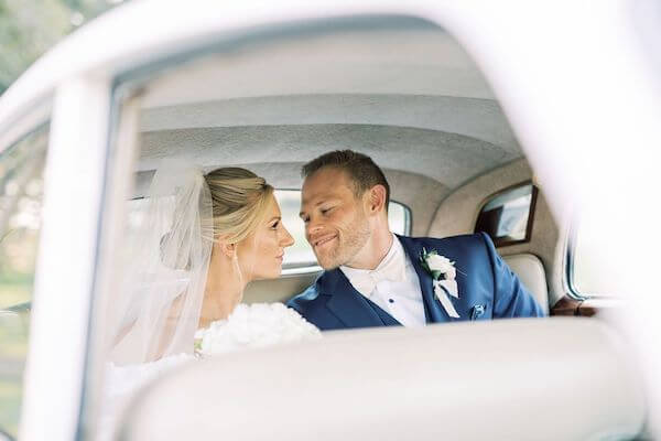 bride and groom in the back of a vintage white rolls Royce