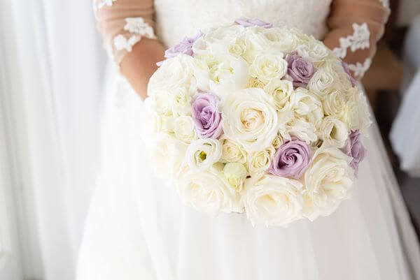 bride carrying a white and lavender rose bouquet