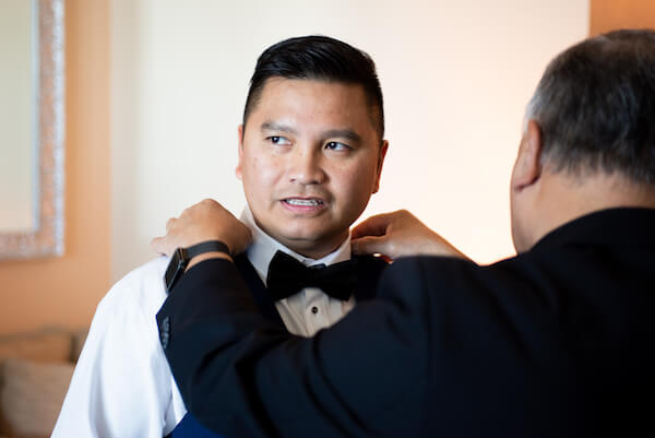 Groom getting dressed for his Opal Sand wedding ceremony