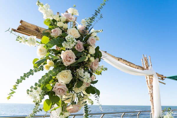 blush and white floral swags on a birch wood wedding structure