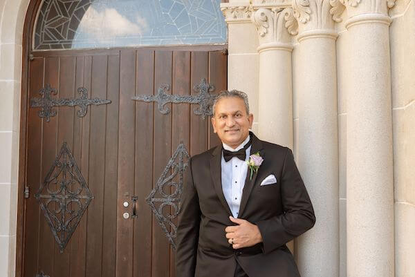 South Asian groom wearing a classic black tuxedo with a lavender rose boutonniere