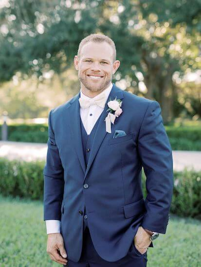 handsome groom wearing a navy blue three piece suit with white bow tie