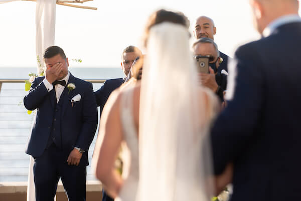 Groom bursts into tears as he sees his bride walking down the aisle during their Opal Sands outdoor wedding ceremony