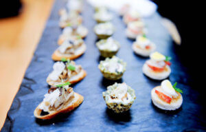 hors d' oeuvres on a slate platter for wedding guests