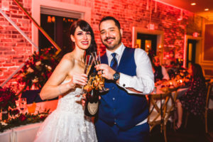 bride and groom toasting with a bottle of Dom Perignon at their downtown St Pete rooftop wedding