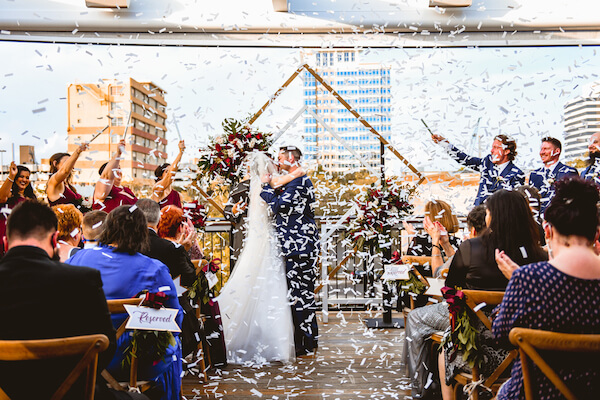 bride and groom sealing their wedding vows with a kiss in an exploding of Flutter Fetti
