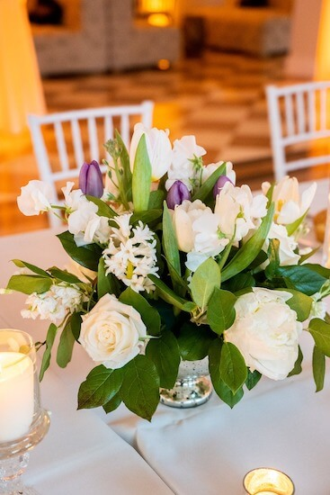 centerpiece of white and purple tulips, peonies and sweetpeas