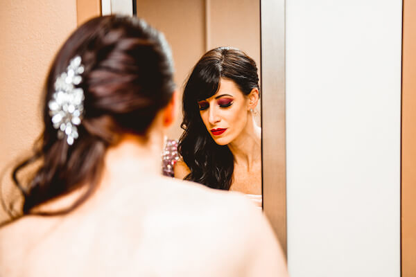 beautiful bride looking at her reflection in the mirror