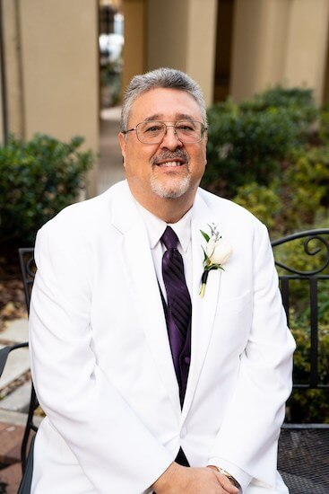 Tampa groom wearing a white suit jacket and dark purple necktie