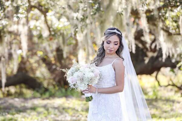 bride in beautiful lace wedding gown with a soft white and pink bridal bouquet