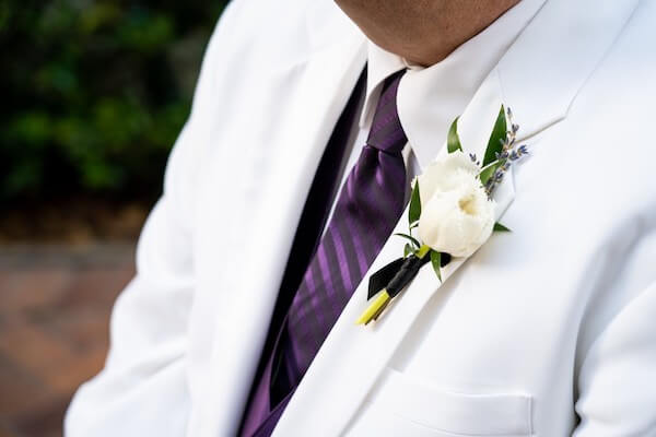 groom wearing a frilly white tulip boutonniere