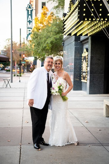 Bride and groom posing for photo in front of the historic Tampa Theater