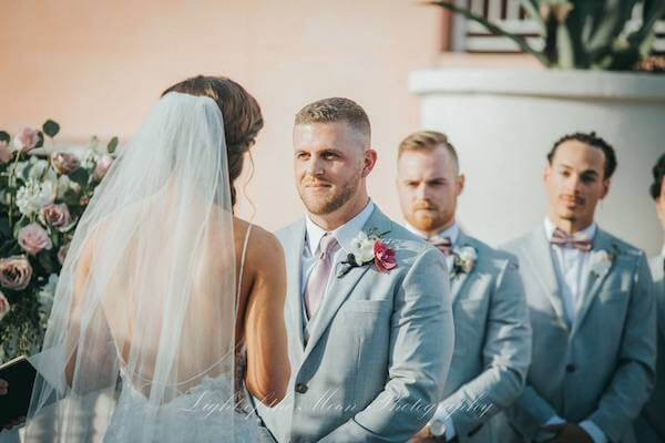 groom looking into his bride's eyes as she recites her wedding vows
