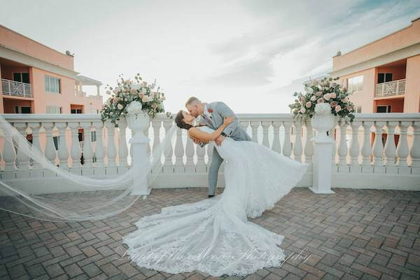 groom dipping his new bride as they take wedding photos on the sky terrace at the Hyatt Clearwater Beach