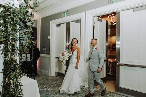 bride and groom taking a sneak peak at their wedding reception at the Hyatt Clearwater Beach