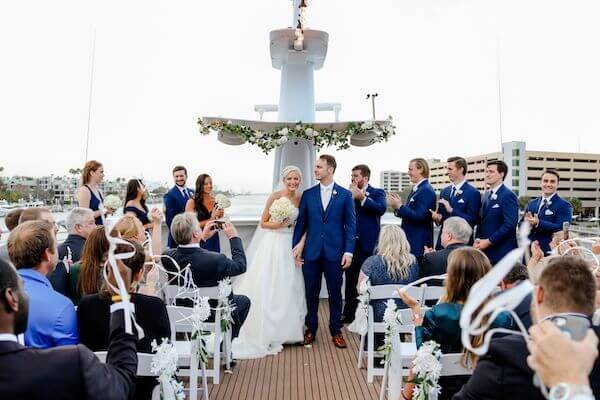 Newlyweds recessional in a flutter of ribbon wands on the upper deck of the Yacht StarShip in Tampa