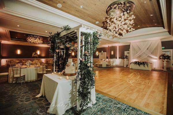 ballroom at the Hyatt Clearwater Beach set with a white trellis over a beautiful wedding cake